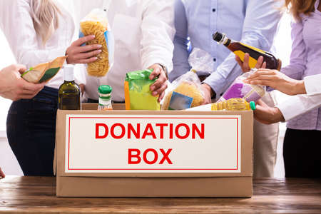 Group Of People Donating Food In Donation Box
