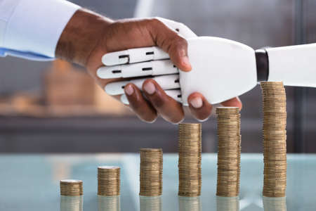 Increased Stack Of Coins In Front On Man Shaking Hand With Robot Stock Photo