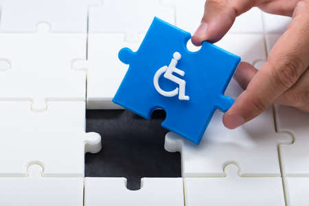 Human hand solving jigsaw puzzle with blue piece having handicap icon