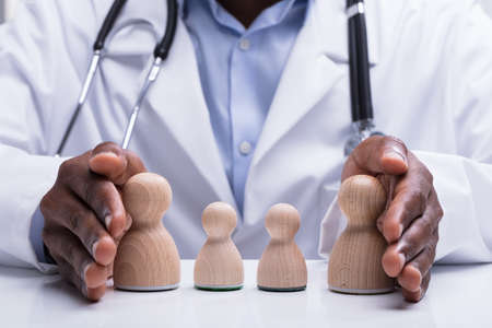 Close-up Of Doctor With Stethoscope Protecting Wooden Pawn Family With His Hand On Desk