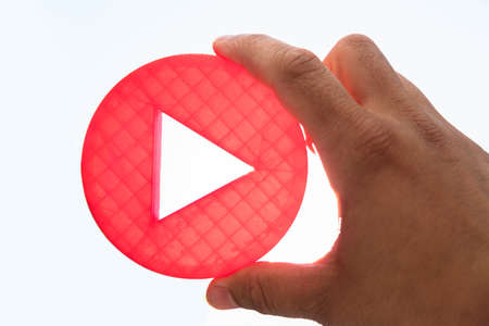 Close-up of a persons hand holding red play icon