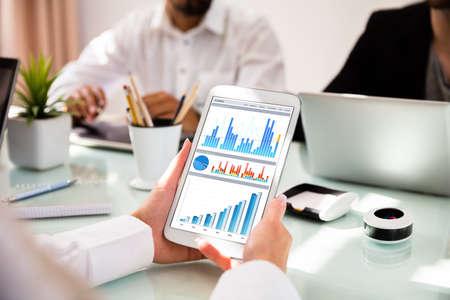 Nahaufnahme der Hand einer Geschäftsfrau unter Verwendung des digitalen Tabletts mit den Graphen auf dem Bildschirm