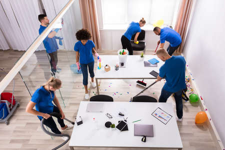 Group Of Young Janitors Cleaning Office With Cleaning Equipment After Party