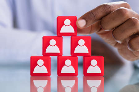 Mans Hand Holding A Top Of Blocks Pyramid With People Icons Over Red Blocks
