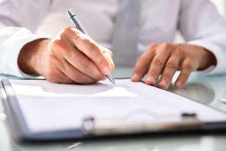 Businessmans Hand Filling Contract Form With Pen