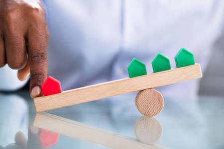 Human Hand Balancing Red And Green Miniature House On Wooden Seesaw Over The Reflective Desk