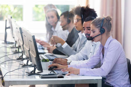 Young Customer Service Executives Using Earphones Working In Call Center
