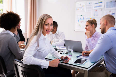 Portrait Of A Happy Young Businesswoman Sitting In Office Stock Photo