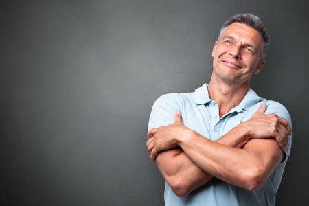 Portrait Of A Mature Man Hugging Himself Against Grey Background