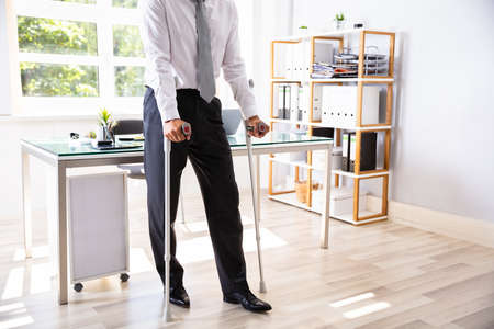 Disabled Businessman With Crutches Standing In Office Stock Photo