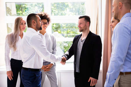 Young Businessman Shaking Hands With His Partner At Workplace