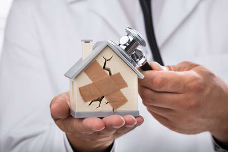 Doctors hand examining broken house with stethoscope on reflective desk