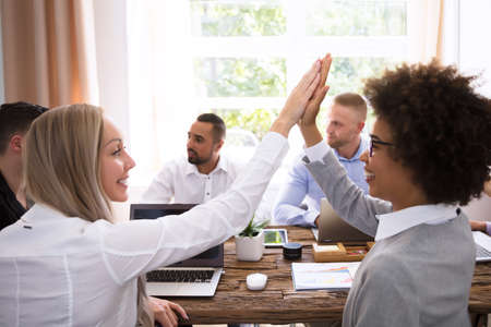 Two Smiling Young Businesswomen Giving High Five In Office