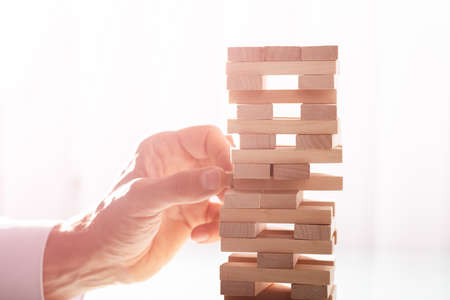 Close-up Of A Businessmans Hand Stacking Wooden Blocks