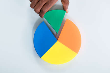 Overhead View Of Human Hand Taking Green Piece Of Pie Chart On Gray Background