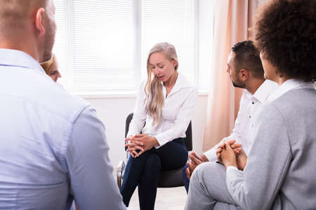 People Listening To Young Woman Talking About Her Problems In Group Therapy Session Stock Photo