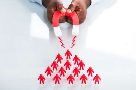 Close-up Of A Human Hand Attracting Red Human Figures With Horseshoe Magnet On White Background Stock Photo