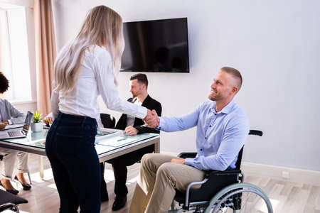 Disabled Happy Businessman Shaking Hand With His Female Colleague In Office