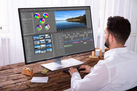 Jonge mannelijke redacteur bewerken van video op computer op de werkplek Stockfoto