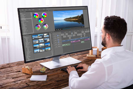 Young Male Editor Montage vidéo sur ordinateur au travail Banque d'images