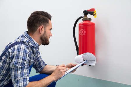Nahaufnahme eines jungen männlichen Technikers, der Feuerlöscher überprüft, der auf Dokument schreibt