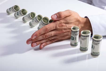 High Angle View Of A Person Stopping Falling Rolled Up Banknotes On Desk Banque d'images