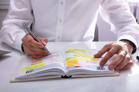 Businessman's Hand Writing Schedule In Diary On Office Desk 免版税图像