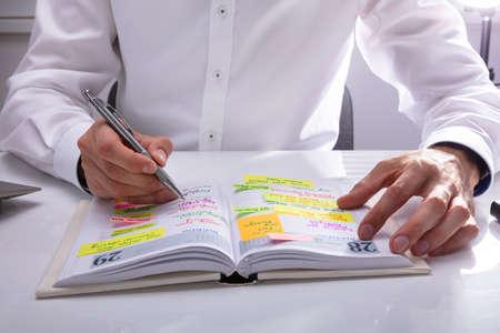 Horario de escritura a mano del empresario en el diario en el escritorio de oficina
