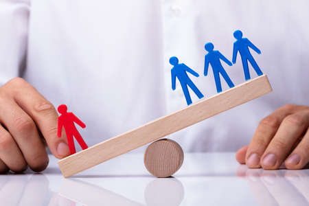 Businesspersons Finger Showing Red Human Figure Competing Against Blue Team On Wooden Seesaw