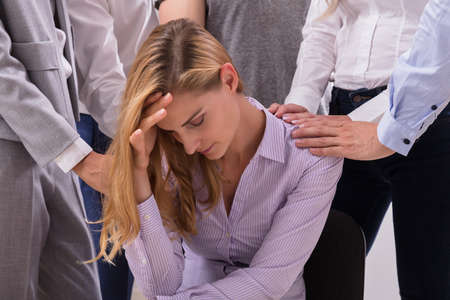 Close-up Of People Consoling Unhappy Young Woman