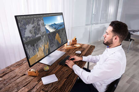 Young Man Editing 3D Landscape On Computer Over Wooden Desk