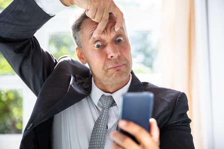 Nahaufnahme eines verängstigten reifen Geschäftsmannes, der Handy-Bildschirm betrachtet