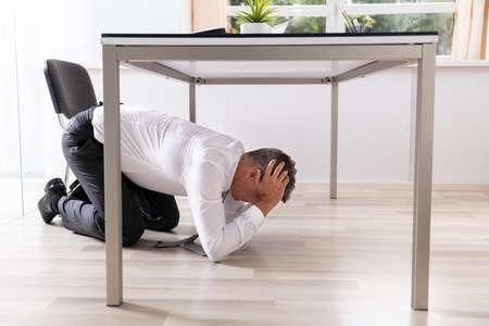 vista lateral de un hombre de negocios maduro asustado que oculta debajo de la mesa