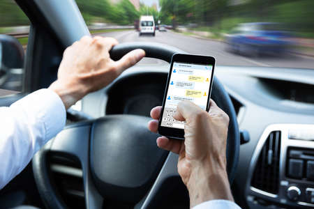 Close-up Of A Mans Hand Typing Text Message On Mobile Phone While Driving Car Фото со стока