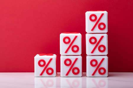 Stack Of Increasing Cubic Blocks With Percentage Symbol In Front Of Red Backdrop Stock Photo