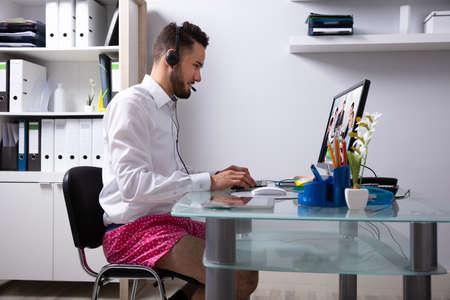 Junger Geschäftsmann, der Kopfhörer während Videokonferenz auf Computer verwendet