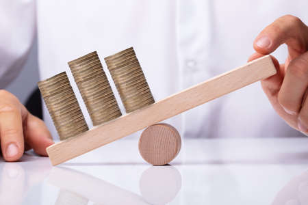 Human Hand Balancing Golden Stacked Coins On Wooden Seesaw