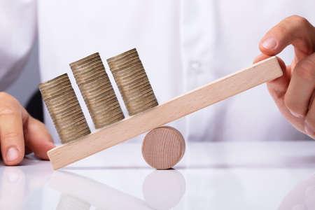 Menschliche Hand, die goldene gestapelte Münzen auf hölzerner Wippe balanciert Standard-Bild