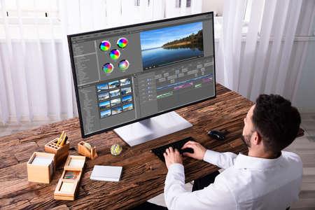 Jonge mannelijke editor video bewerken op computer op de werkplek Stockfoto