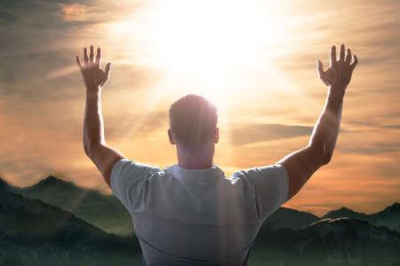 Hombre levantando su brazo delante del paisaje de montaña