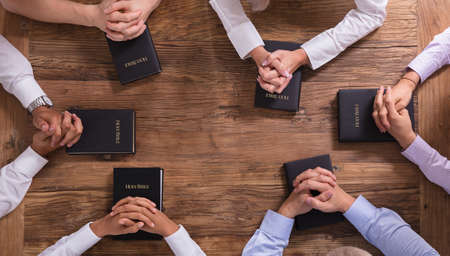 High Angle View Of People's Praying Hands On Holy Bible Stock Photo