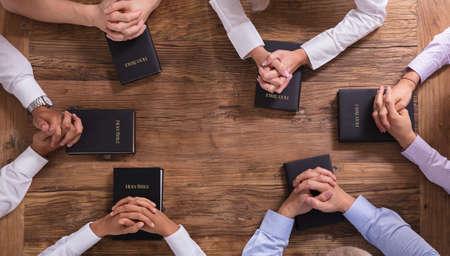Wysoki kąt widzenia modlących się rąk ludzi na Świętej Biblii