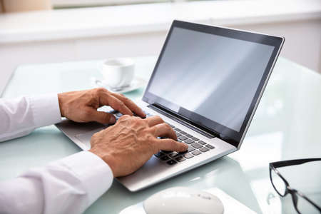Businessman's Hand Using Laptop While Writing Schedule In Diary
