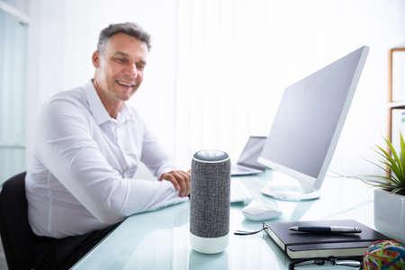 Hombre maduro sonriente escuchando música en el altavoz inalámbrico