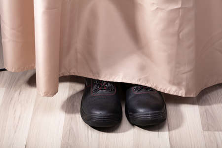 View Of A Person Shoe's Hiding Behind Curtain Stock Photo