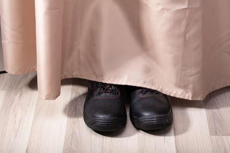 Vue d'une chaussure de personne se cachant derrière le rideau
