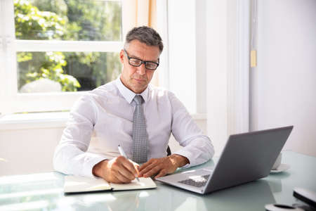 Mature Businessman Writing Schedule In Diary With Pen Over Desk