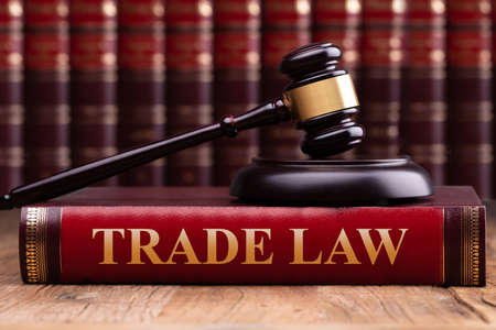 Soundboard And Gavel On Trade Law Book Over Wooden Table