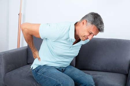 Reifer Mann, der auf Sofa sitzt und unter Rückenschmerzen leidet
