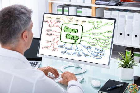 Close-up de un empresario haciendo gráfico de mapa mental en la computadora en el lugar de trabajo